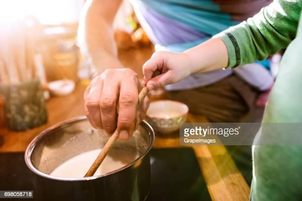 Vater zu Hause in der Küche kochen, Baby Sohn in die Schlinge, älterer Sohn, ihm zu helfen.