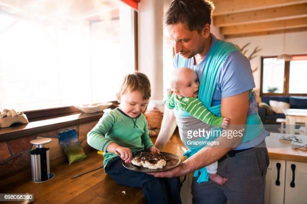 Vater zu Hause in der Küche Essen, Baby Sohn in die Schlinge, älterer Sohn Essen