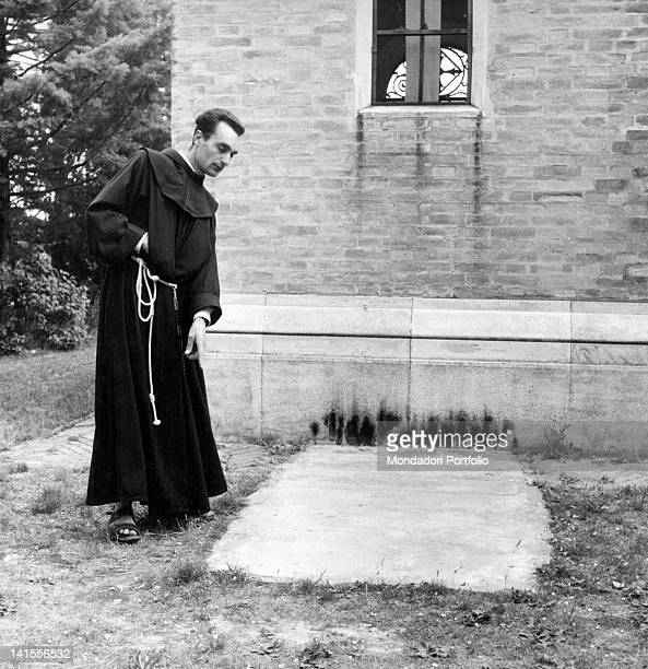 Father Augustine Ferrini pointing at the concrete slab beneath it is believed the remains of Benito Mussolini are buried Dovadola May 1955