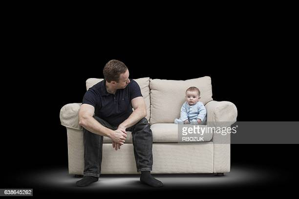 father & baby on couch - black ginger baby stock photos and pictures