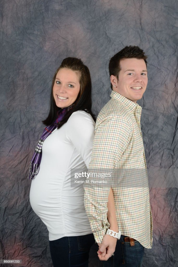 Father back to back with pregnant mother (8 months pregnant) smiling & holding hands : Stock Photo