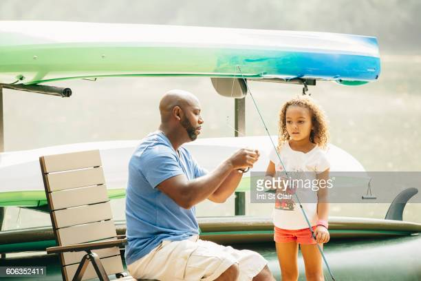 Father baiting fishing hook for daughter at lake