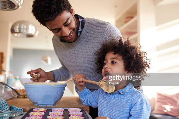 Father Baking Cake With Son In Kitchen At Home