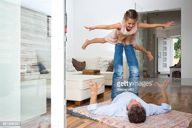 Father balancing his daughter on his feet