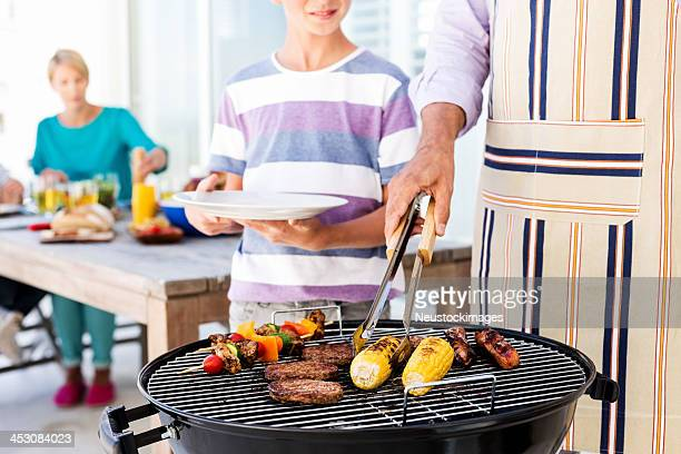 Father Barbecuing Food On Grill With Family In Background