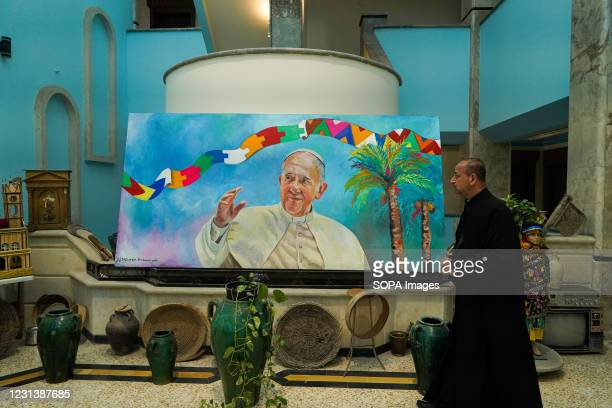 Father Bashar Kadhia, the official in charge of the Saint Paul Monastery looks at a painting of Pope Francis days before his historic visit to Iraq....