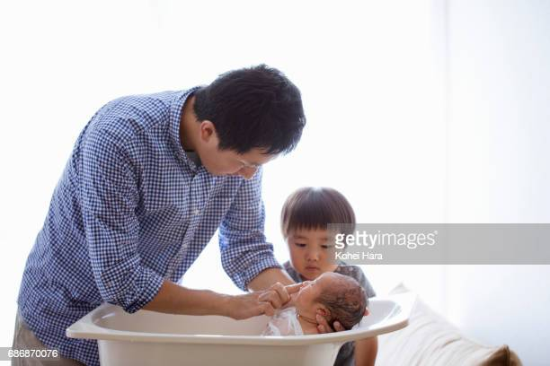 father bathing his baby in baby bath and his son watching it. - taking a bath stock pictures, royalty-free photos & images