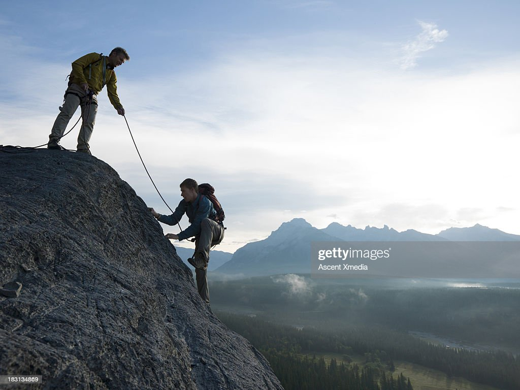 Father belays son up rock cliff above mountains : Stock Photo