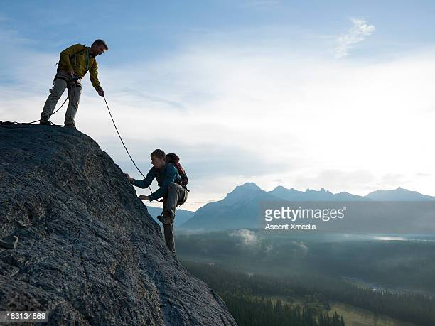 Father belays son up rock cliff above mountains