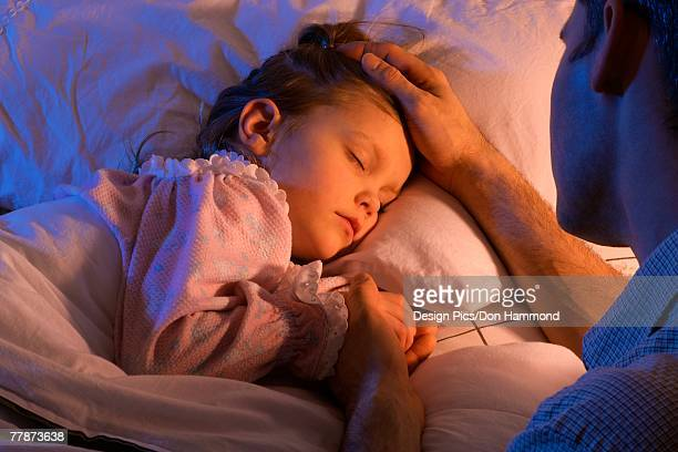 Father beside sleeping daughter bed