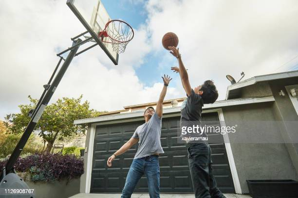 father blocking while son making basketball score - blocking sports activity stock pictures, royalty-free photos & images