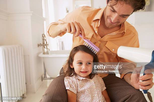 Father blowdrying daughter's (2-4) hair in bathroom, close-up