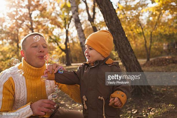 Father blowing bubbles with baby boy in park during autumn