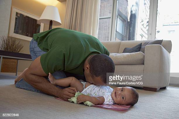 Father blowing on his infant daughter's stomach