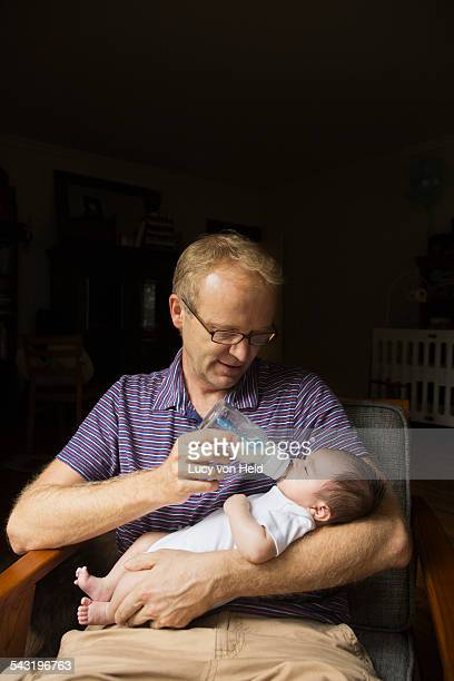 Father bottle feeding baby in armchair