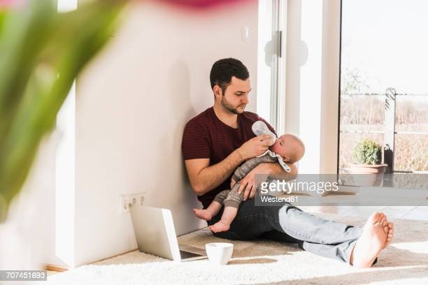 Father bottle feeding his baby son