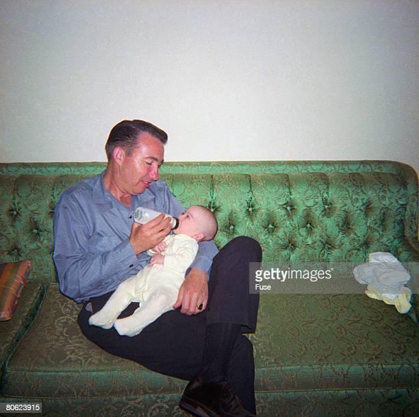 Father bottle-feeding baby on sofa