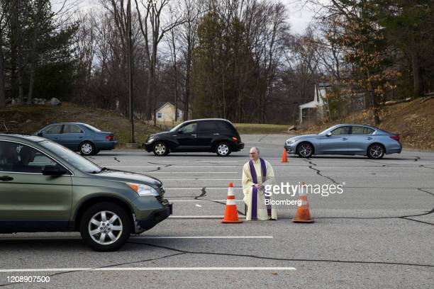 Father Brian Mahoney waits to hear a parishioner's confession in the parking lot of the St Mary's Church in Chelmsford, Massachusetts, U.S., on...