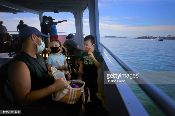 Father brings out a snack for his kids on board the Fort Independence ferry as it rides in the waters around Boston on July 29, 2020. While many...