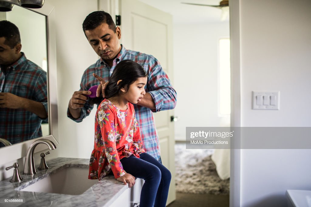 Father brushing daughters hair in bathroom : Stock Photo