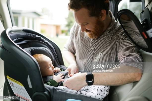 father buckling baby boy (2-3 months) in car seat - バックル ストックフォトと画像