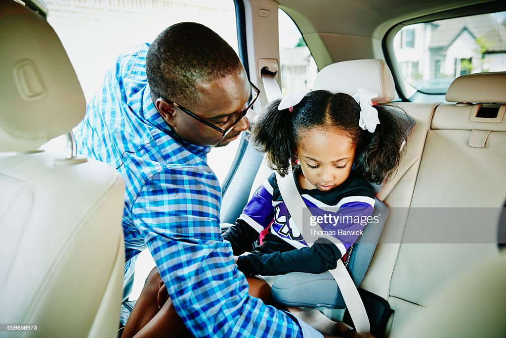 Father buckling daughter into car seat in car : Stock Photo