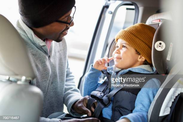 Father buckling son in car seat