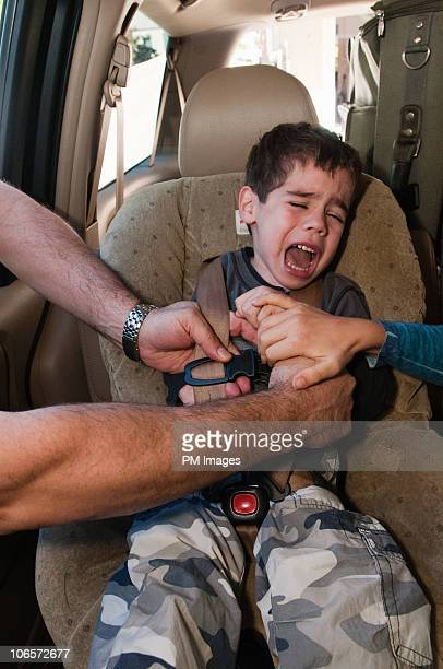 Father buckling son into car seat, boy crying
