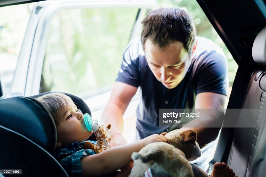 Father buckling son into car seat : Stock Photo