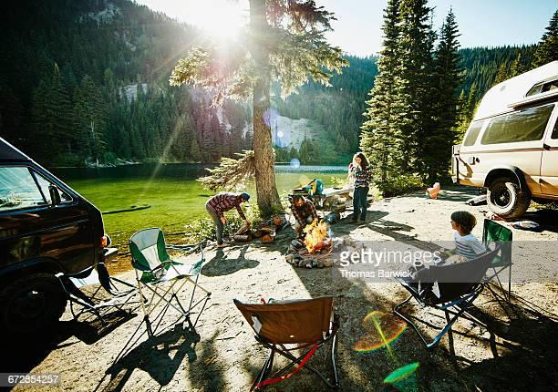 father building fire while family sets up camp - landfahrzeug stock-fotos und bilder