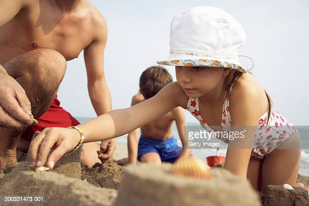 Father building sandcastles with son and daughter (7-9), close-up