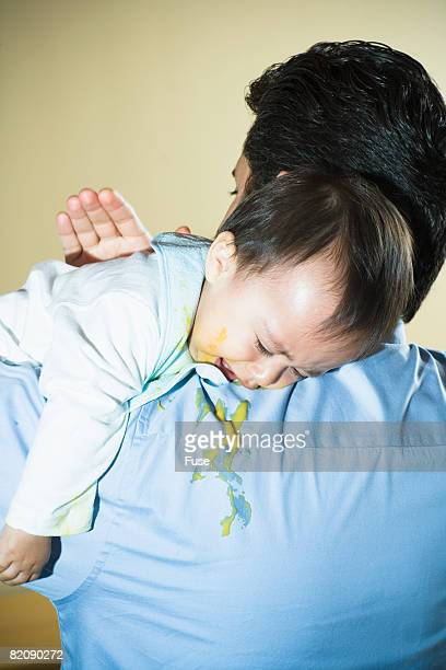 father burping infant son - vomiting stock photos and pictures