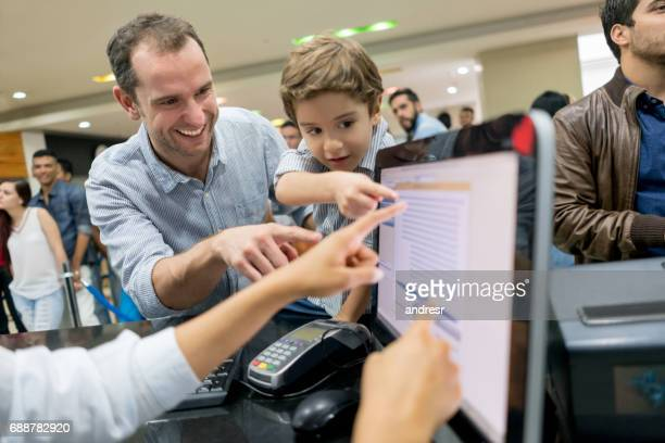 Father buying movie tickets with his son and choosing thir seats
