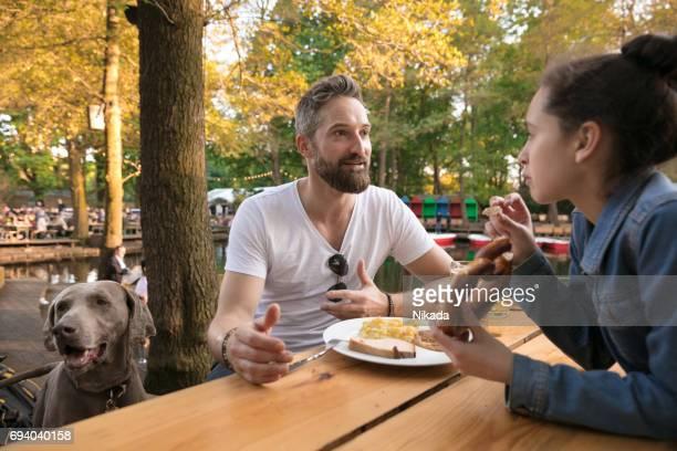 Père de chien parlant à la fille tout en ayant les aliments à table