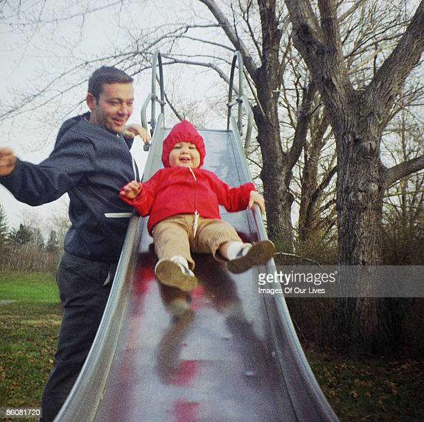Father by son sliding down slide