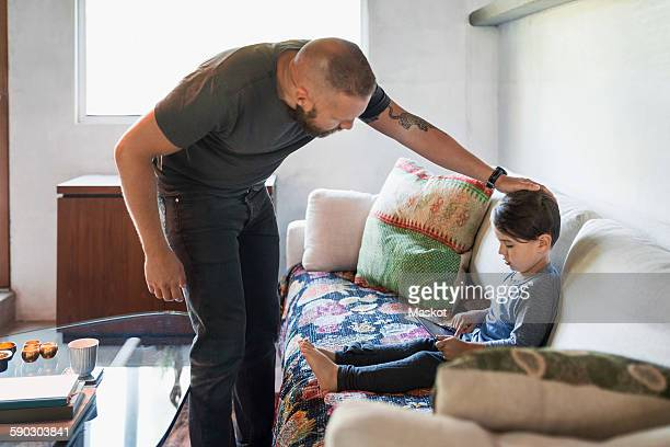 Father caressing son using digital tablet on sofa at home
