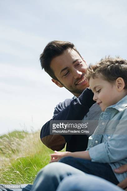 father caressing son's hair outdoors - close to stock pictures, royalty-free photos & images