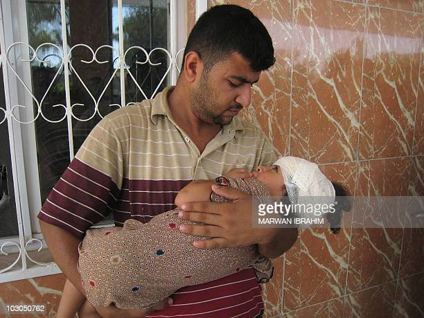 A father caries his injured daughter out of the general hospital in the northern Iraqi city of Kirkuk on July 23 following a blast which seriously...