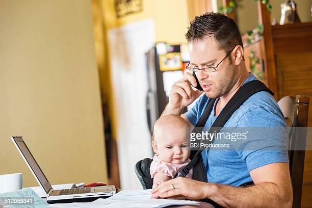 Father caring for baby daughter while working in home office