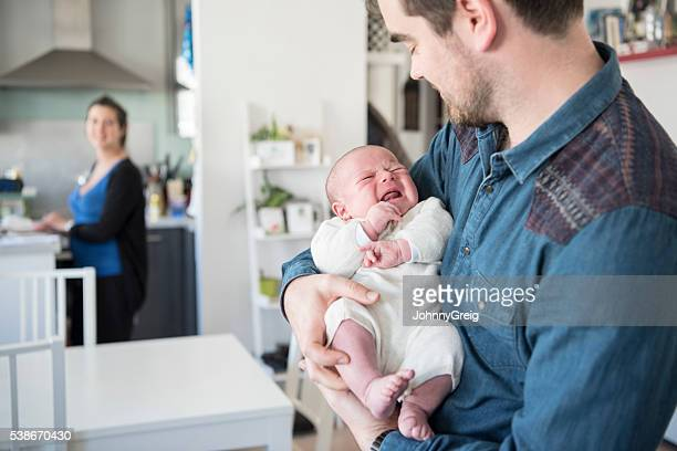 Father caring for newborn baby son as mother looks on