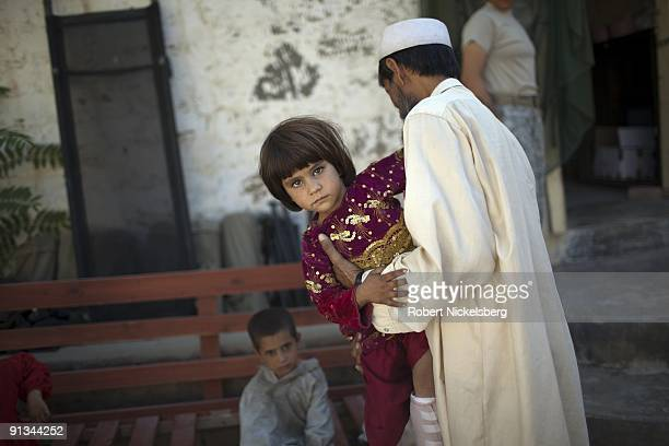 A father carries his 4year old daughter Talwaza out of a US Army clinic at Forward Operating Base Blessing in Nangalam Afghanistan September 6 2009...