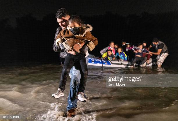 Father carries his child to shore after crossing the Rio Grande in a dinghy at the U.S.-Mexico border on April 9, 2021 in Roma, Texas. A surge of...