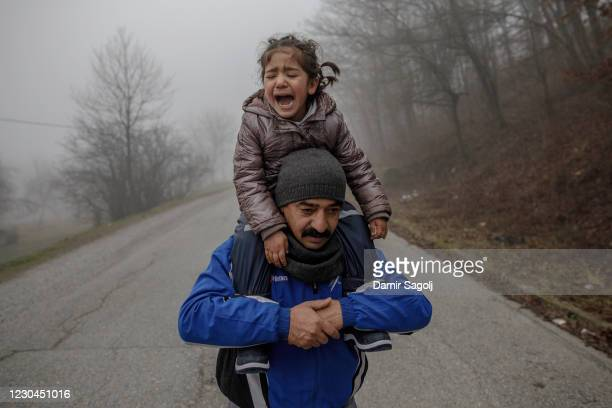 Father carries his crying daughter as members of a migrant family from Afghanistan approach Croatia's border from Bosnian side in an attempt to cross...