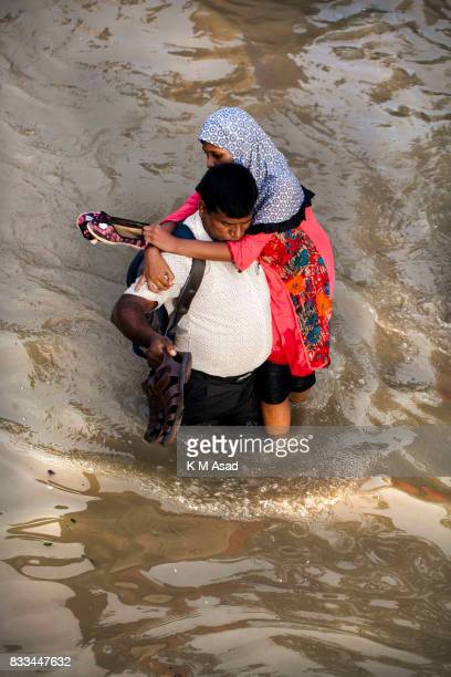 AGRABAD DHAKA CHITTAGONG BANGLADESH Father carries his daughter through a flooded area of ChittagongPeople traveling in flooded areas in Chittagong...