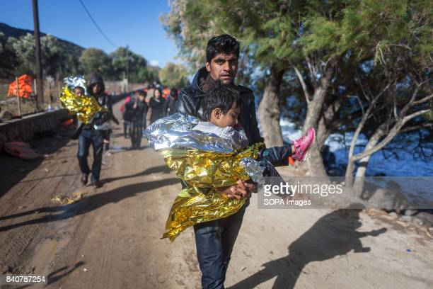 A father carries his son in his arms on the shores of Skala Skamineas where the boat that took them from Turkey to the Greek coasts just arrived Ten...