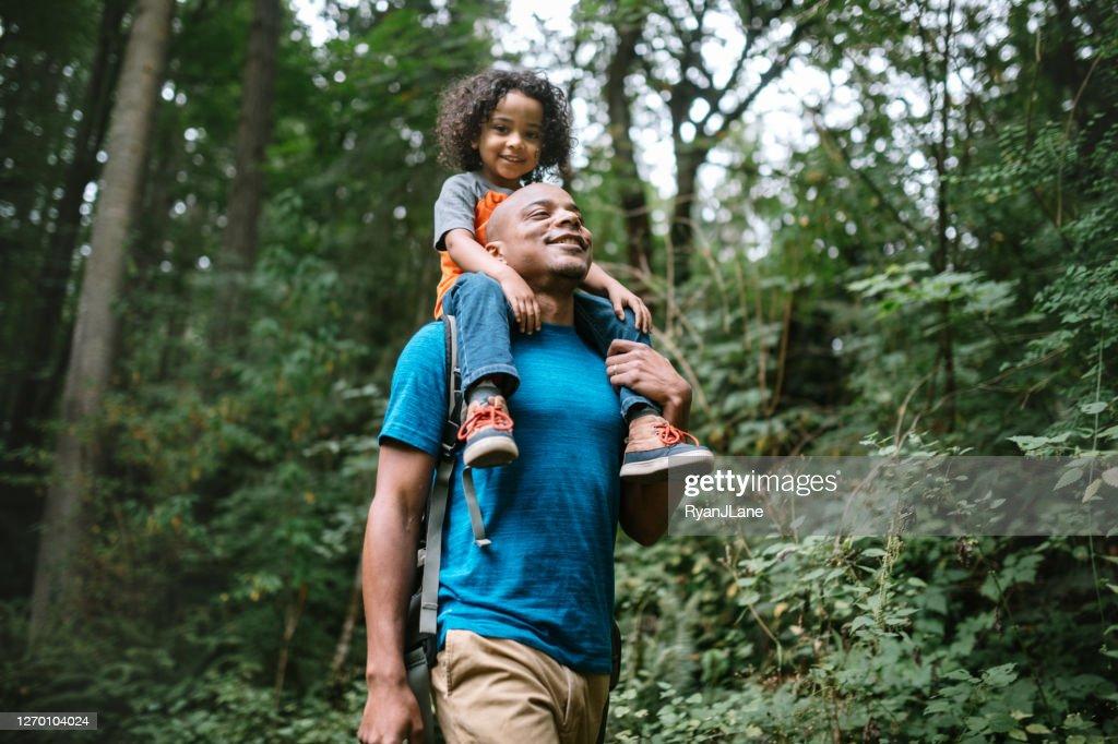 Pai carrega filho em caminhada pela trilha florestal no Noroeste do Pacífico : Foto de stock