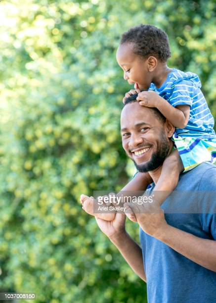 Father Carrying 2 Year Old on Shoulders