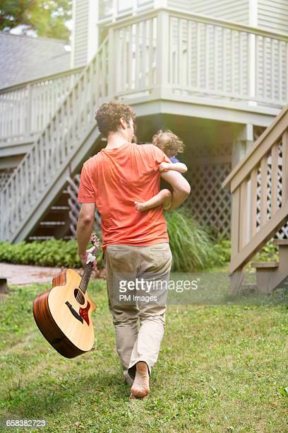 Father carrying baby and guitar