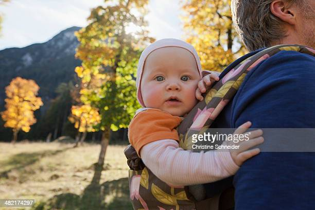 Father carrying baby daughter in carrier