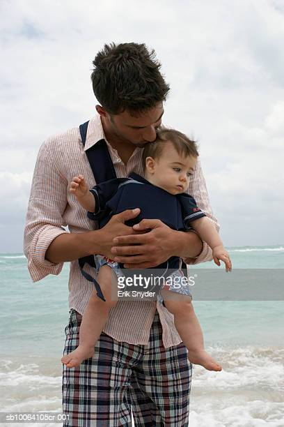 father carrying baby daughter (15-18 months) on beach - strap stock photos and pictures